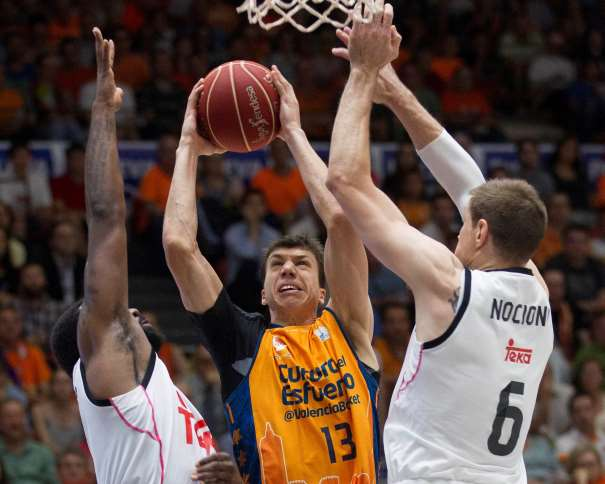 En esta foto podemos ver a Vladimir Luchitch, Alero serbio del València, y a Andres (Chapu) Nosioni, Ala-Pívot argentino del Madrid, en una acción de juego del Tercer Partido de estas Semifinales ACB 2015, cerca de uno de los aros, cerca de una de las 2 canastas