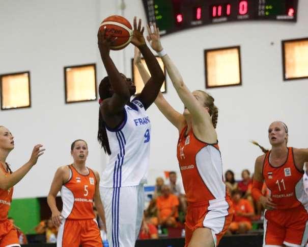 En esta foto podemos ver a la Jugadora francesa Mousdandy Djaldi-Tabdi que Hoy disputará la Final del EuroBasket Femenino U20 de FIBA Europe en la isla de Lanzarote, en las Localidades de Teguise y Tinajo. La foto es del Partido de Semifinales de Ayer, contra Holanda y Djaldi-Tabdi está ejecutando una lanzamiento a Canasta con la oposición de una jugadora holandesa mientras otras 3 holandesas observan la jugada