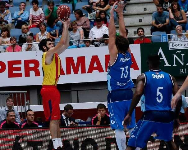 En esta foto podemos ver a Álex Abrines, jugador del Barcelona, ejecutando un lanzamiento a canasta mientras el Jugador del GBC David Doblas intenta punterarlo y el que fuera cortado Taquan Dean observa