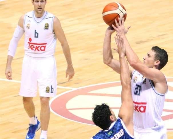 En esta foto podemos ver a Jaycee Carroll ejecutando un lanzamiento a canasta, con la oposición de un Defensor del Baurú, mientras observa Andrés Nosioni, durante el Segundo Partido de la Copa Intercontinental de Clubes FIBA 2015 de la que el Madrid ha conseguido ser el Segundo Equipo Europeo en conseguirla