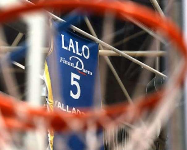 En esta foto podemos ver, a través de una de sus canastas, a través de la red y del aro que la componen, la camiseta retirada del fallecido Lalo García en lo alto del Pabellón Polideportivo Pisuerga de Valladolid
