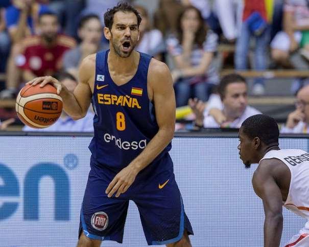En esta foto podemos ver a José Manuel Calderón, botando el balón con su mano derecha y haciendo indicaciones verbales, defendido por un Jugador de la Selección de Angola