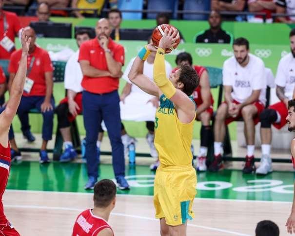 En esta foto podemos ver cómo David Andersen ejecuta un lanzamiento a canasta rodeado de defensores serbios, en el Partido de semifinales de los Juegos Olímpicos de Rio 2016. También podemos ver, de fondo, el Banquillo de Serbia, con su Seleccionador de pie observando la jugada