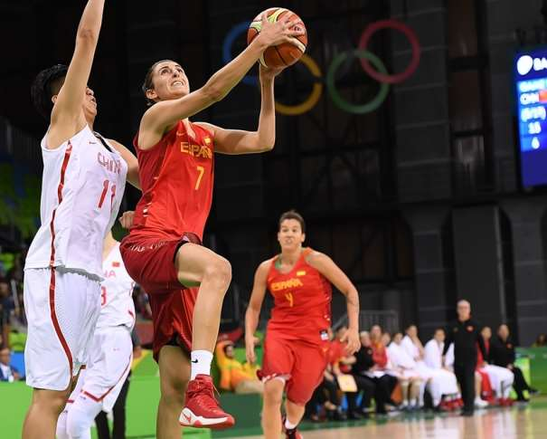 En esta foto podemos ver a Alba Torrens entrando a canasta, sin que las defensoras chinas puedan evitarlo, con los aros olímpicos de fondo, como testigos
