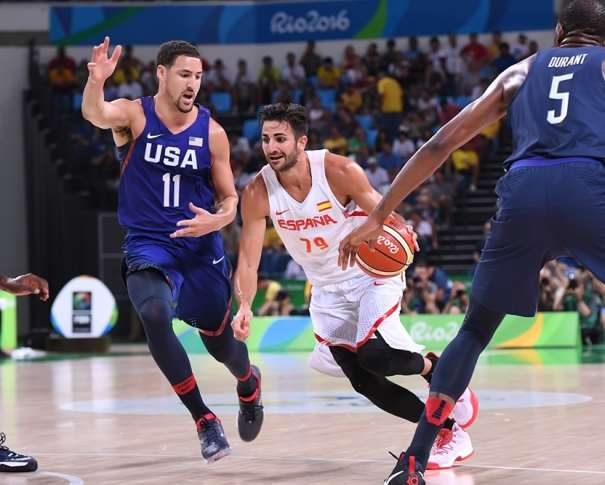 En esta foto podemos ver a Ricky Rubio rodeado de 3 Jugadores de la Selección NBA de USA, tratando de irse de Kyrie Irving, con bote, con mano derecha, mientras Kevin Durant y otro defensor más están atentos a posibles Ayudas Defensivas