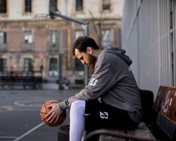 """En esta foto podemos ver a Sergio Rodríguez (""""Chacho""""), Jugador de los Philadelphia 76ers de la NBA, con el balón entre sus manos, sentado en un banco, en una pista exterior"""