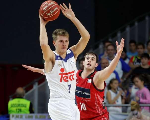 En esta foto podemos ver a Luka Dónchitch con el balón en sus manos, por encima de la cabeza, intentando evitar la Defensa del Jugador del Zaragoza Sergi-García