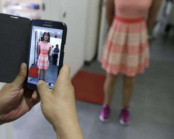 """En esta foto podemos ver cómo Qian Hongyan, """"la chica baloncesto"""" de China, posa para que le hagan una foto, luciendo sus piernas (ortopédicas) nuevas"""
