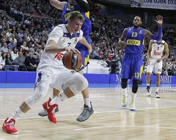 En esta foto podemos ver al Jugador esloveno del Madrid, Lúka Dónchitch, defendido por el estadounidense del Maccabi Colton Iverson. También podemos ver a los también estadounidenses Sonny Weems y Anthony Randolph