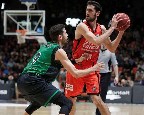 En esta foto podemos ver al Exterior del València, Joan Sastre, protegiendo el balón ante la defensa del Jugador del Joventut de Badalona, Sergi Vidal. También podemos ver, de fondo, una de las canastas, la del fondo contrario a la jugada, y a uno de los árbitros