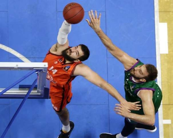 En esta foto podemos ver al Interior montenegrino del València, Boian Dubllevitch, capturando un rebote, ante la tímida oposición de un jugador del Málaga