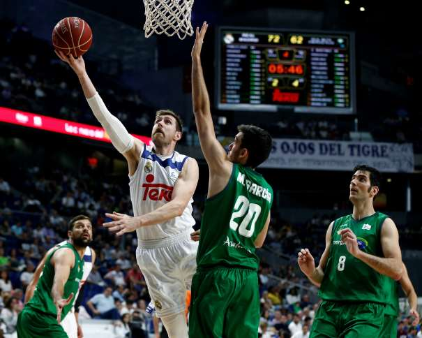 En esta foto, facilitada por la Liga ACB, podemos ver a Andrés Nocioni a punto de Anotar con su mano derecha, debajo de la canasta, superando a los Defensores del Sevilla