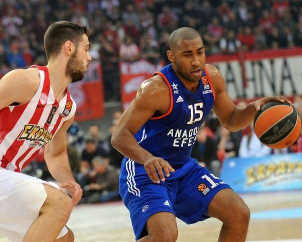 En esta foto, facilitada por la Euroliga de Baloncesto, podemos ver a Jayson Granger conduciendo el balón, con bote, con su mano izquierda, ante la oposición de un Defensor del Olympiacós