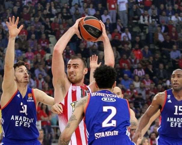 En esta foto, facilitada por la Euroliga de Baloncesto, podemos ver a Nikola Milutinov rodeado por defensores del Efes, con el balón por encima de la cabeza, protegiéndolo