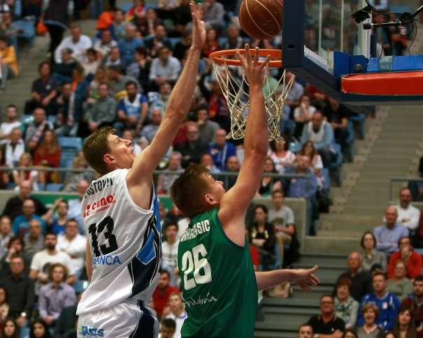 En esta foto, facilitada por la Liga ACB, podemos ver a Artem Pustovyi intentando taponar un lanzamiento a canasta (desde debajo de ésta) de u jugador del Sevilla. Tanto el lanzamiento a canasta como el intento de tapón se realizan utilizando la mano y el brazo derechos de ambos jugadores
