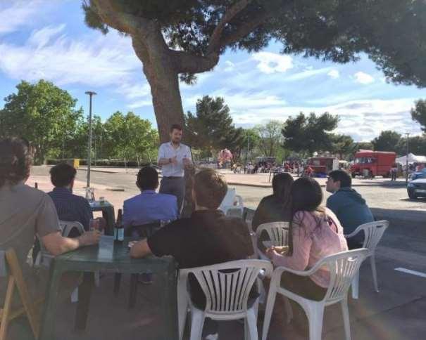 En esta imagen podemos ver un Detalle de una de las Catas de la I Feria de la Cerveza Artesanal de San Sebastián de los Reyes, en el que se puede ver al expositor-conductor de la misma, a la sombra de un árbol