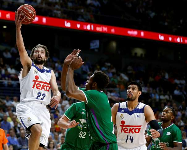 En esta foto, facilitada por la Liga ACB de Baloncesto, podemos ver al Jugador Exterior del Madrid, al balear Sergio Llull haciendo una entrada a canasta con su mano derecha sin que ningún defensor del Málaga pueda hacer nada por evitarlo