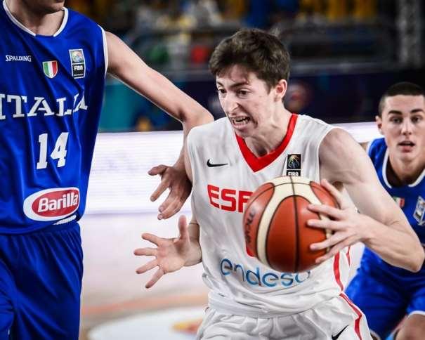En esta foto, facilitada por la FIBA, Federación Internacional de Baloncesto, podemos ver al Máximo Anotador de la Selección U19 Masculina en el Partido de Semifinales, en el de su Primera Derrota, Aleix Font, intentando superar, con bote, con mano izquierda, a los Defensores de Italia