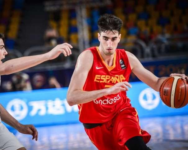 En esta foto, facilitada por la FIBA, Federación Internacional de Baloncesto, podemos ver al MVP de la Selección U19 Masculina, Eric Vila, tratando de irse de un defensor de la Selección de la República Argentina, con bote, con mano izquierda
