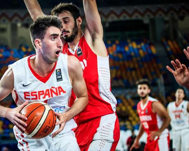 En esta foto, facilitada por la FIBA, Federación Internacional de Baloncesto, podemos ver al MVP de la Selección U19 Masculina, Eric Vila, con el balón entre sus manos, defendido por un Jugador de la Selección de la República Islámica de Irán