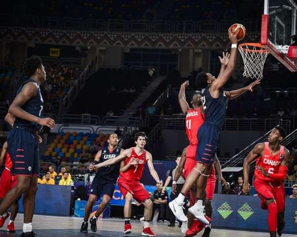 En esta foto, facilitada por la FIBA, Federación Internacional de Baloncesto, podemos ver al MVP de la Selección U19 Masculina de USA en el Partido de Semifinales, en el de su Primera Derrota, Austin Wiley, superando, bajo el aro, con mano derecha, a los Defensores de Canada