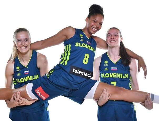 En esta foto, facilitada por la FIBA, Federación Internacional de Baloncesto, podemos ver a 2 Jugadoras de la Selección U20 Femenina de la República de Eslovenia posando para la foto mientas sostienen entre sus brazos a una tercera Jugadora