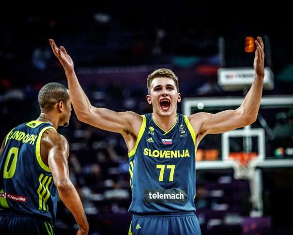En esta foto, facilitada por FIBA, Federación Internacional de Baloncesto, podemos ver al MVP del Primero de los Partidos de Semifinales del EuroBasket 2017, al Exterior Lúka Dónchitch, en un momento de alegría y celebración, levantando los 2 brazos. También podemos ver, de fondo y de espaldas, a su compañero de Equipo ACB y Euroliga y de Selección Eslovena, al estadounidense de nacimiento, nacionalizado esloveno para este Eurobásket, Anthony Randolph
