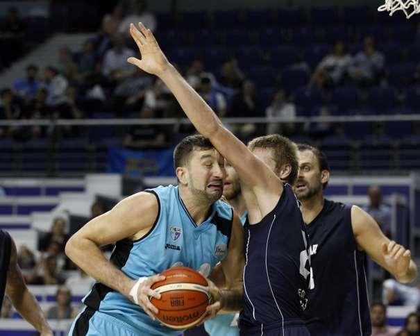 En esta foto, facilitada por la FIBA Basketball Champions League, podemos ver a Goran Suton y a 2 Jugadores del Groningen que intentan pararlo