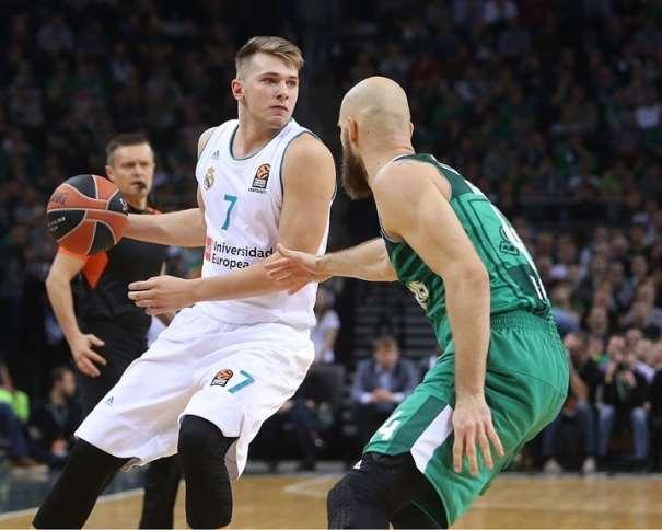 En esta foto, facilitada por la Euroliga de Baloncesto, podemos ver a Luka Dónchitch botando el balón con su mano derecha mientras lo protege de su defensor y mira por encima de su hombro izquierdo para ver lo que está sucediendo en el Partido