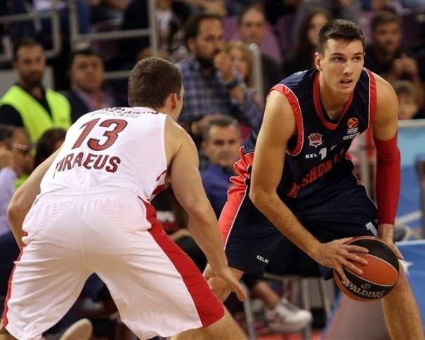 En esta foto, facilitada por la Euroliga de Baloncesto, podemos ver al escolta estadounidense del Baskonia Matt Janning alejado el balón de su defensor, llevándolo, con sus 2 manos, hacia su rodilla izquierda