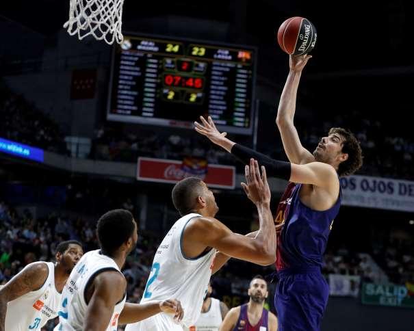 En esta foto, facilitad por la Liga ACB, por la Asociación de Clubes de Baloncesto, podemos ver a Ante Tómitch, pívot croata del Barcelona, elevándose, en Madrid, por encima de los Jugadores del Madrid, para ejecutar un lanzamiento a canasta, un tiro, con su mano derecha, mientras se protege del posible, aunque improbable, tapón con la izquierda