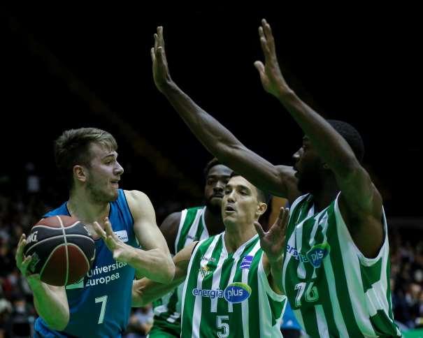 En esta foto, facilitad por la Liga ACB, por la Asociación de Clubes de Baloncesto, podemos ver a Luka Dónchitch rodeado por 3 jugadores del Sevilla, con el balón entre sus 2 manos, protegiéndolo sobre su hombro derecho, el punto más alejado posible de esos 3 defensores