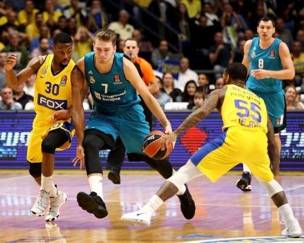 En esta foto, facilitada por la EuroLiga de Baloncesto, podemos ver a Luka Dónchitch yéndose de su defensor, con bote, con mano izquierda, mientras otro defensor intenta hacer una ayuda (defensiva)